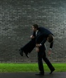 Business man carrying colleague on shoulder, side view
